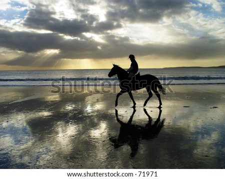 horse rider on Irish beach silhouetted by setting sun. Atlantic Ocean behind.