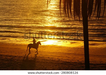 Horse rider silhouette at sunset beach - stock photo