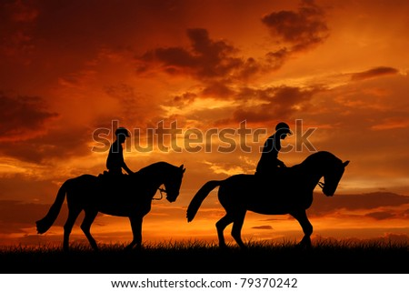 horse riders in the sunset - stock photo