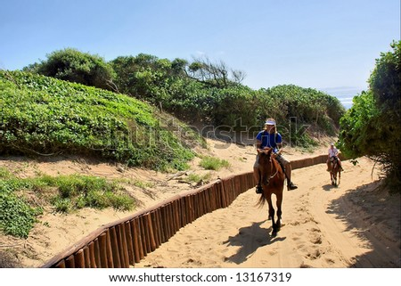 Horse riders on sand road from beach. Shot in Sodwana Bay Nature Reserve, KwaZulu-Natal province, Southern Mozambique area, South Africa.