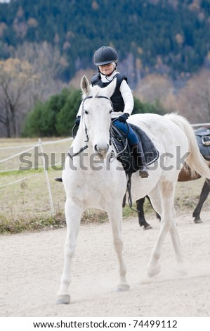 Horse riding - little girl is riding a horse - stock photo