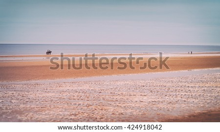 Horse riding on a sandy beach at Druridge Bay, Northumberland, UK. - stock photo