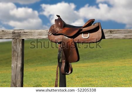 Horse saddle on rural fence - stock photo