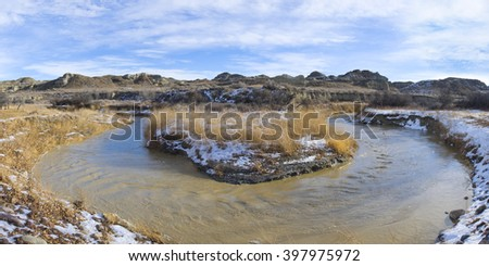 Horse Shoe bend in the fast moving dirty river of the Bad Lands - stock photo