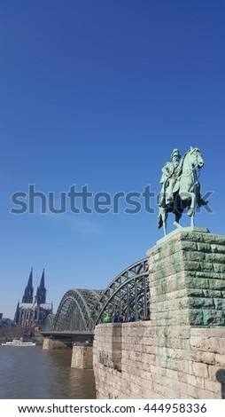 Horse statue near bridge and river with clear blue sky in Germany
