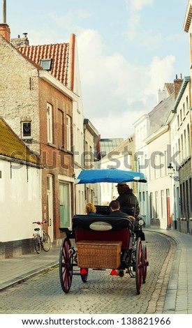 Horse vehicle with tourists on a narrow small street in Bruges - stock photo