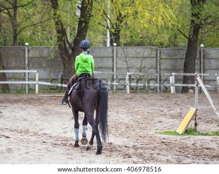 horseback boy riding a horse in spring time - stock photo