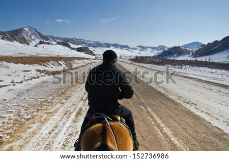 Horserider in mongolian wilderness - stock photo