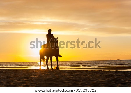 Horseriding at the beach on sunset background. Baltic sea. Vibrant multicolored summertime outdoors horizontal image. - stock photo