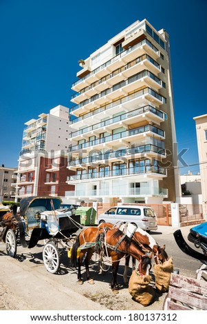 Horses and carriage in front of a modern building at Vina del Mar, Chile. - stock photo