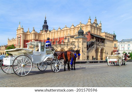 Horses and carts on the market in Krakow with a view of the hall - stock photo