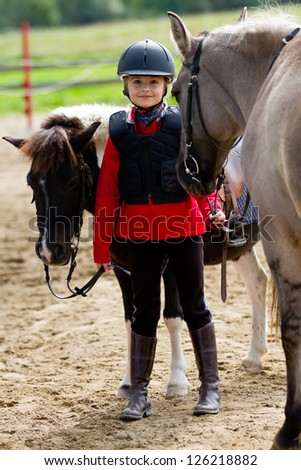 Horses and lovely equestrian girl - stock photo