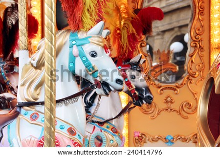 Horses on a carnival Merry Go Round Carousel.  - stock photo