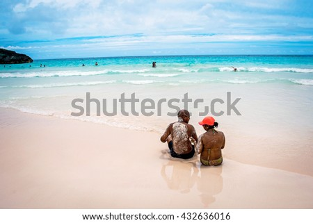HORSESHOE BAY, BERMUDA - MAY 26 - A couple relaxes on the pink sand beach in Horseshoe Bay on May 26 2016 in Bermuda. - stock photo