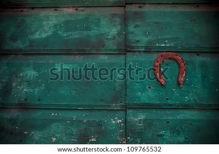 Horseshoe on green wood background - stock photo