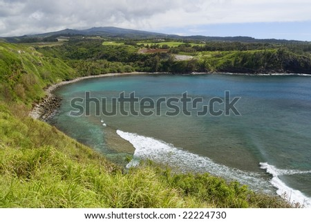 Horseshoe shaped Honolua Bay on Maui, Hawaii shows beautiful azure water and coral reef underneath - stock photo