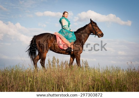 Horsewoman in blue dress on the blue sky background