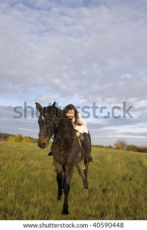 Horsewoman lay down on the withers of the horse. - stock photo