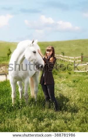 horsewoman on field with white horse. Portrait