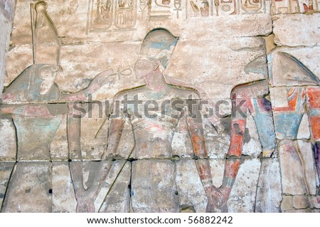 Horus, Ramses and Khnum Falcon headed god Horus and goat headed creator god Khnum with Ramses II between them.  Temple to Osiris at Abydos, Egypt.
