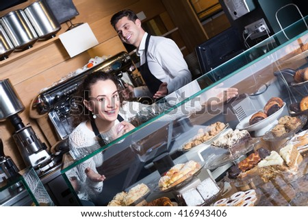 Hospitable man and friendly girl with delicious cream pies at bakery display  - stock photo