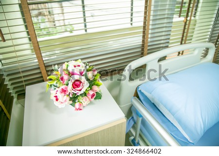 Hospital: Focus On Flowers Next To Hospital Bed - stock photo