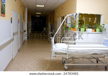 hospital hall with a bed at foreground - stock photo