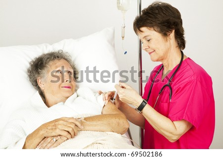 Hospital nurse giving an elderly female patient an injection in her arm. - stock photo