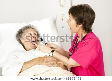 Hospital nurse uses and otoscope and tongue depressor to examine a patient. - stock photo