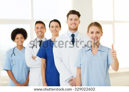 hospital, profession, gesture, people and medicine concept - group of happy doctors showing thumbs up at hospital - stock photo