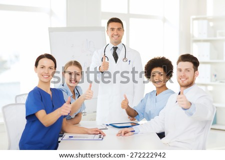 hospital, profession, medical education, people and medicine concept - group of happy doctors meeting on presentation or conference at hospital and showing thumbs up gesture - stock photo