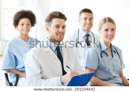 hospital, profession, people and medicine concept - group of happy doctors with clipboard on seminar in lecture hall at hospital