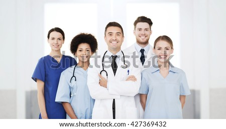 hospital, profession, people and medicine concept - international group of happy doctors at hospital
