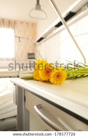 Hospital room with flowers on bedside table