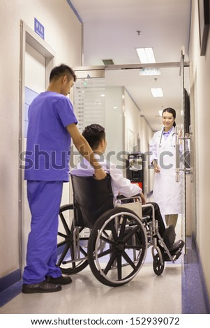 Hospital Staff Pushing Patient In Wheelchair - stock photo