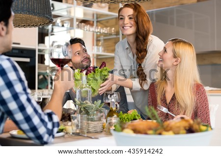 Host woman serving salad to guests at home. Smiling woman serving salads to her friends at home. Happy smiling people eating together for lunch. Group of friends enjoying meal at home together - stock photo