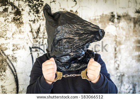 Hostage in handcuffs and with a bag on head - stock photo