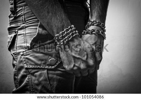 Hostage. Male hands with chain wrapped around them, prisoner concept - stock photo