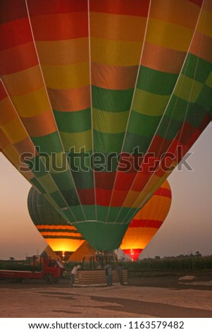 Hot air ballons getting ready to take off in Egypt at dawn, with the flame lighting up the balloon
