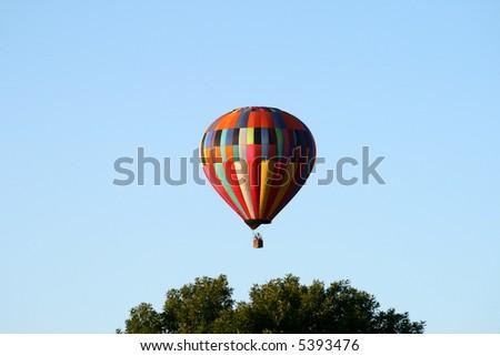 Hot air balloon above treetops - early morning - stock photo