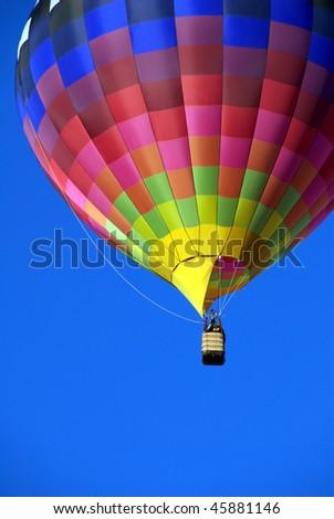 Hot air balloon against brilliant blue sky - stock photo