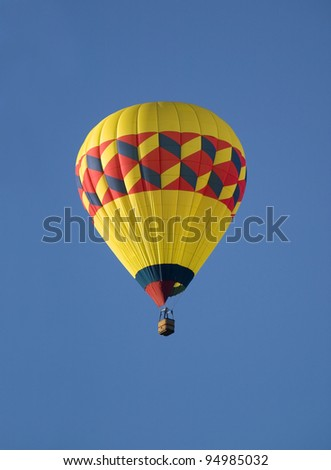 Hot air balloon floating across a blue sky