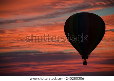 Hot-air balloon floating among pink and orange clouds at dawn