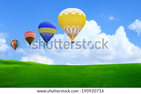 Hot air balloon floating in the sky over green grass - stock photo