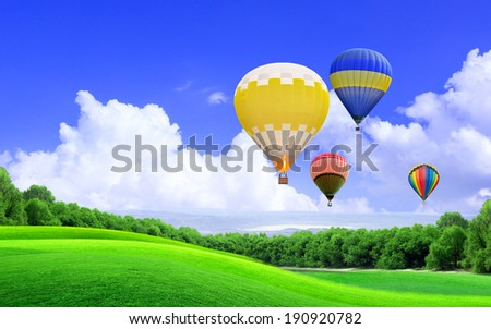 Hot air balloon floating in the sky over the hill - stock photo
