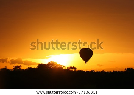 Hot air balloon flying at sunrise over Masai Mara Park, Kenya