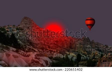 Hot air balloon flying over Cappadocia with dark red sun - stock photo