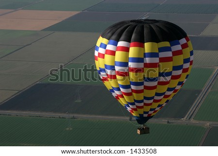 hot air balloon flying over farmlands - stock photo