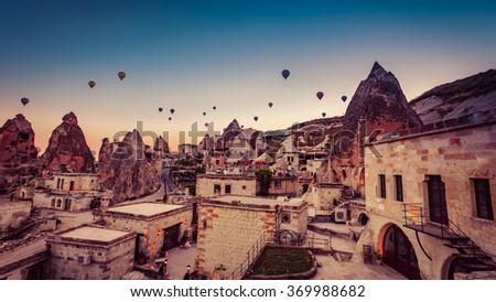Hot air balloon flying over rock landscape at Cappadocia Turkey - stock photo