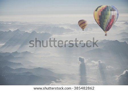 Hot air balloon flying over snowcapped mountain - stock photo